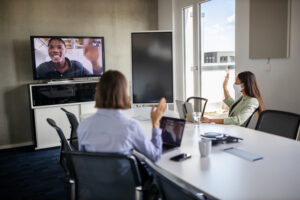 Hybrid workplace: team mates work together remotely and in the conference room.